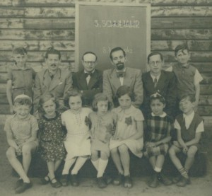 Photograph at camp Westerbork, 1942. Children and teachers near the school. Betti sitting, third on the right.