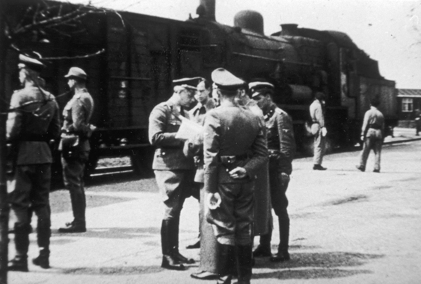 Gemmeker met bewakers in kamp Westerbork bij de gereedstaande trein, 1944.