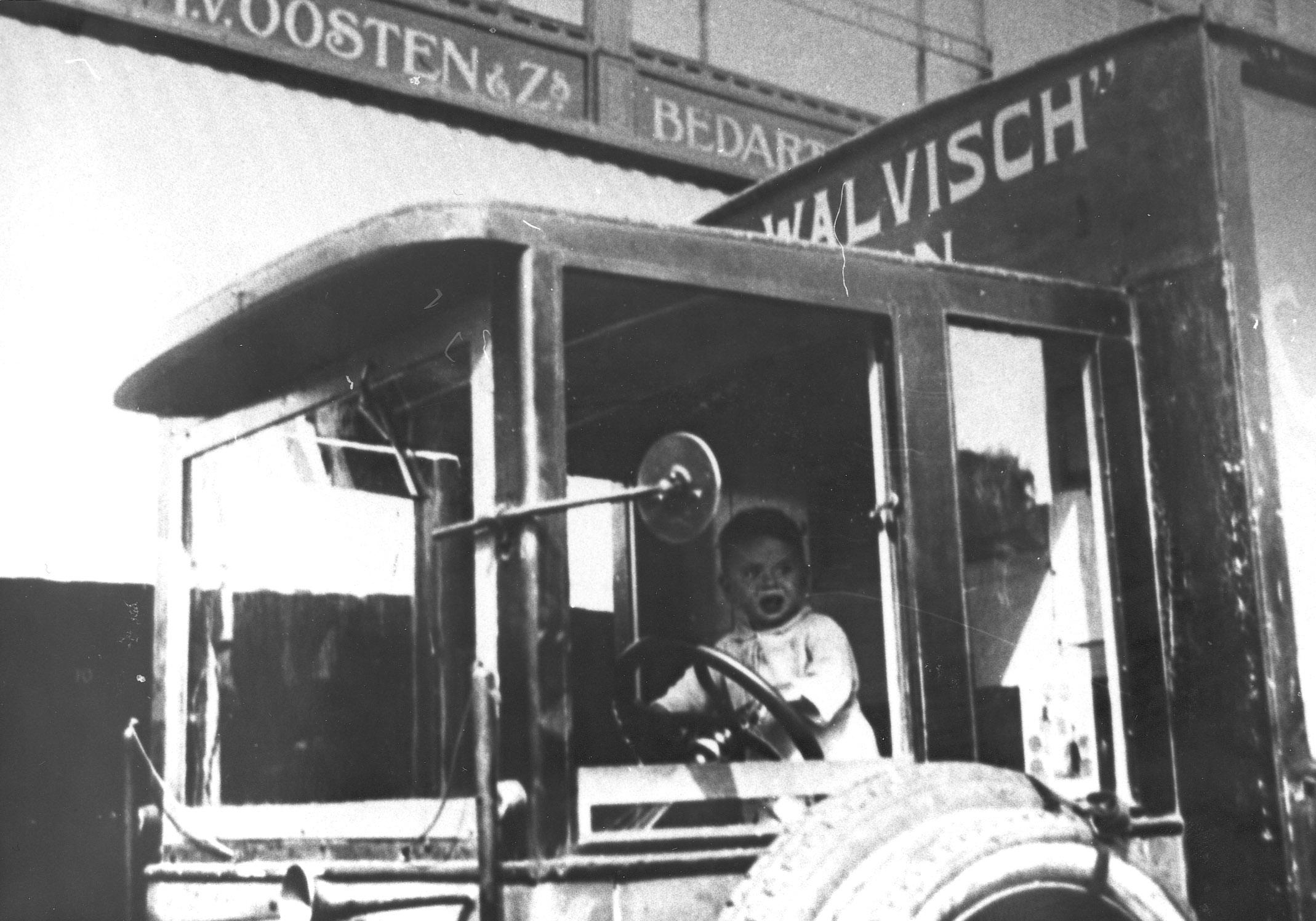 Leo van Oosten als klein jongetje in de vrachtauto van zijn vader.